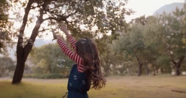 Dívka si hraje s bublinami v oboru