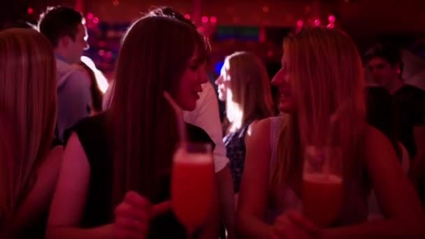 Mädchen, die einander in einer Bar mit Cocktails Toasten