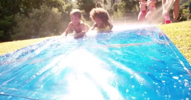 Afro girl and friends playing on a water slide