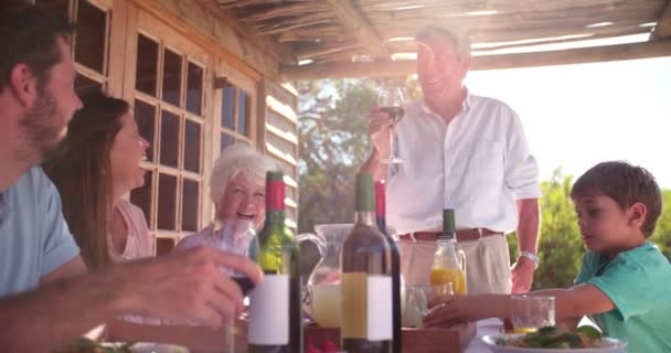 Grandfather toasting his family at a meal