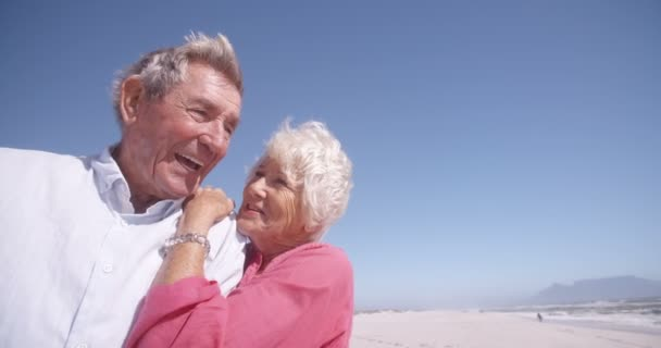 Laughing elderly couple on the beach together