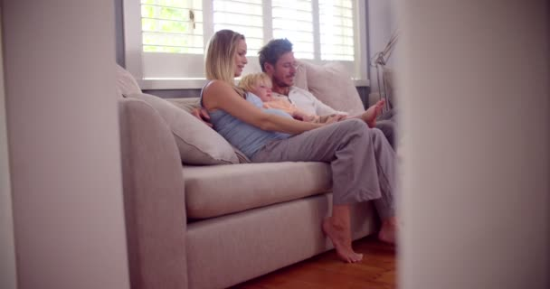 Boy on couch with parents touching his moms pregnant belly