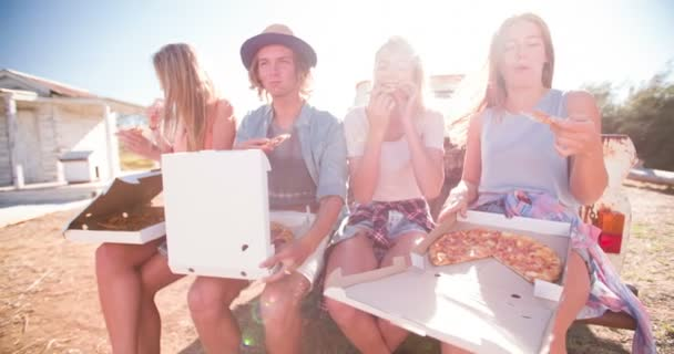 Friends laughing and enjoying pizza on a summer day