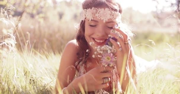 Usmívající se dívka hippie v parku držení kytice