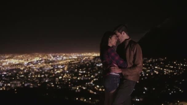 Mladý pár objímat v noci s městem za