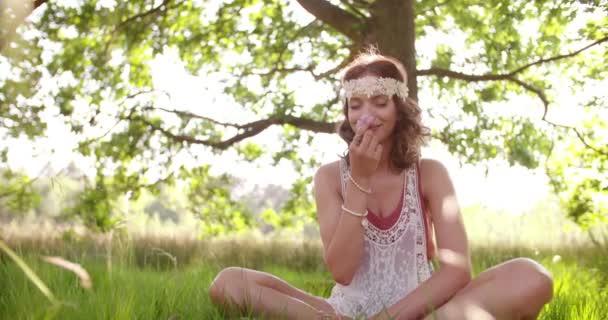 Hippie dívka vonící květinu v letním parku