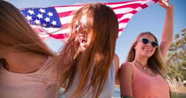 Cool teen friends smiling and holding an American flag