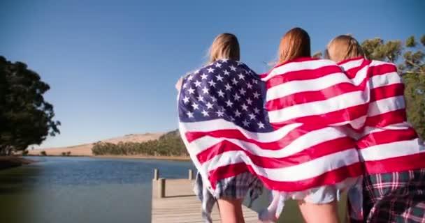 Teenage girls running with american flag