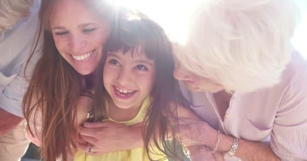 Směje se holčička s její matkou a babičkou