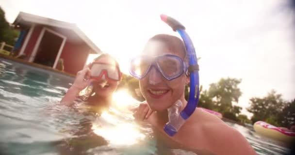couple in pool wearing snorkelling gear