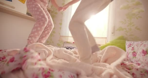 Girls wearing pyjamas jumping on a bed