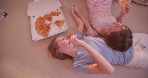 Holky, ležící na podlaze a jíst pizzu