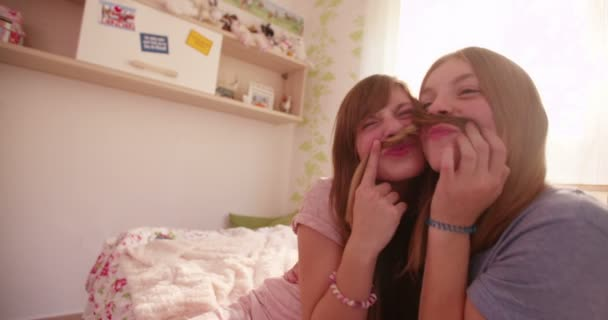 Girls holding each others hair as moustaches