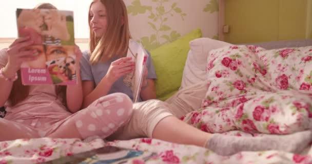 girl showing her friend fashion magazine