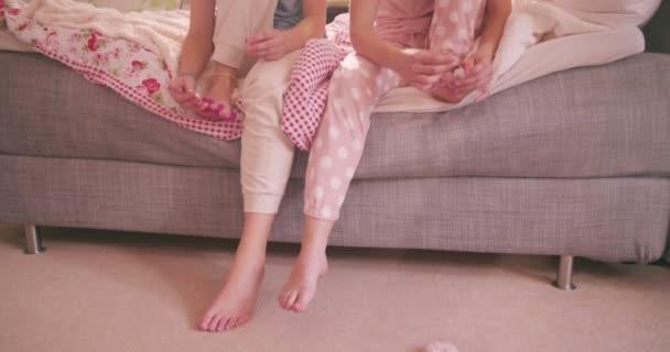 Adolescent girls in pyjamas painting toenails