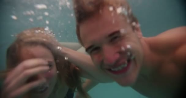 Couple swimming underwater in a pool