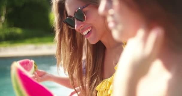 Girls in sunglasses eating fresh watermelon