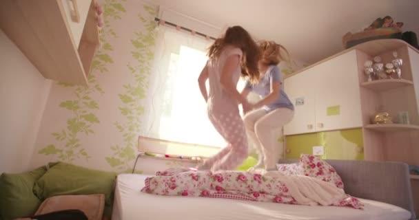 Girls wearing pyjamas jumping on a bed