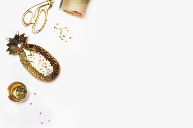 Gold woman items on table. Feminine scene, glamour style. White background mock up. Flat lay, party desk. Table view, workspace. Pineapple, gold bag, Golden shears, confetti.