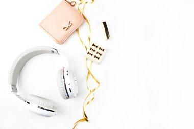 Music headphones, gold ribbon and blush handbag on white background top view. Mock-up. Feminine scene. header site or hero site. Blog image. Flat lay