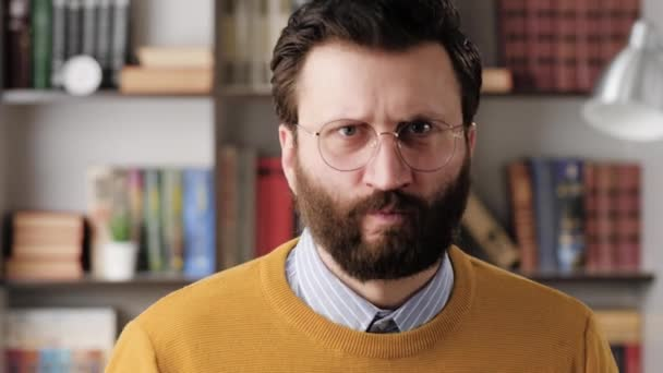 Angry man, rage. Angry annoyed bearded man in glasses in office or apartment room looking at camera and hits table with his fist, pencils fly to sides. Close-up and slow motion