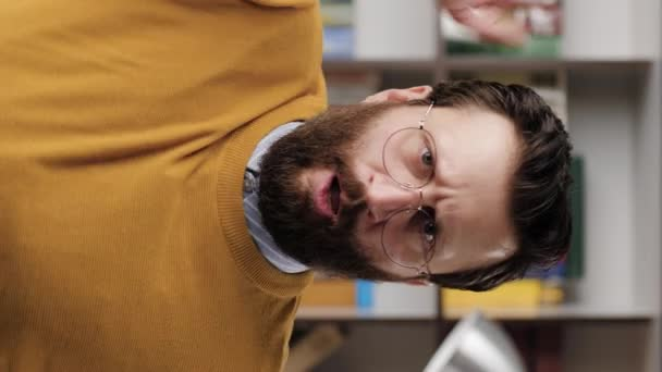 Angry man, rage. Vertical video of angry annoyed bearded man in glasses in office or apartment room looking at camera and hits table with his fist, pencils fly to sides. Close-up and slow motion