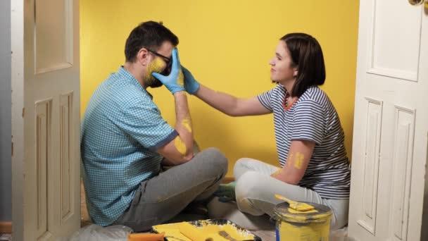 Nástěnné malby, renovace pokojů, slzy radosti. Pár mužů a žen potřísněných barvou sedí na podlaze, muž pláče, zakrývá si obličej modrými rukavicemi, žena ho utěšuje. Zpomalený pohyb