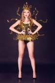 sexy diskotéku žena oblečená v jedinečný zlatý kostým s kovovou křídla. Ideální pro stylový klub, disco a módní události