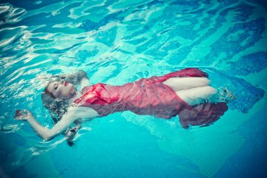 Young sexy woman floating on swimming pool in red dress. beauty shot
