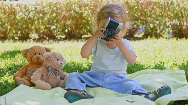 Aranyos kis gyerek kezében egy vintage film kamera és fotózás a Teddy maci