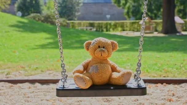 Aranyos kis plüssmackó áll egyedül egy hintán egy üres parkban egy gyönyörű, napos napon..