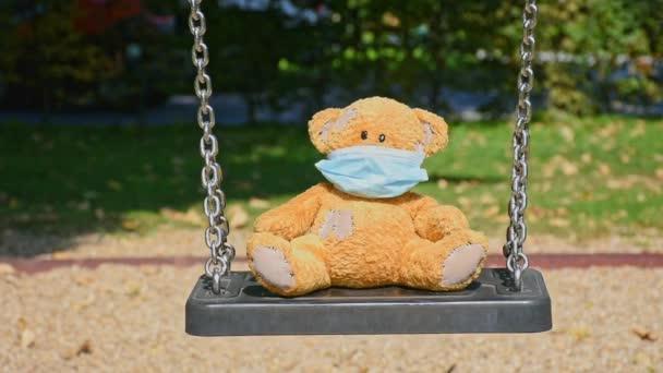 Magányos kis plüssmackó orvosi maszkot visel, egy hintán áll a parkban egy gyönyörű napsütéses napon. Üres játszótér, betegség COVID-2019 betegség koncepció