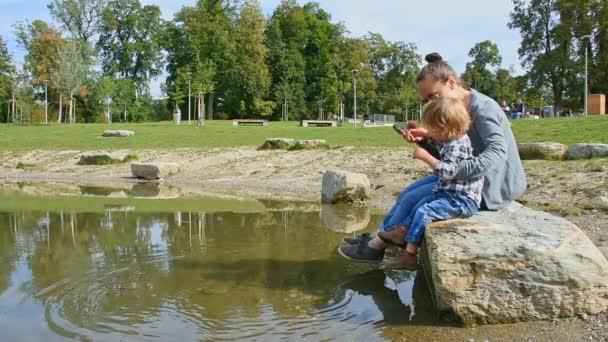 Junge Mutter und süßer kleiner Junge haben Spaß, Steine ins Wasser zu werfen. Freizeit- und lustige Outdoor-Aktivitäten für Kinder im Sommer