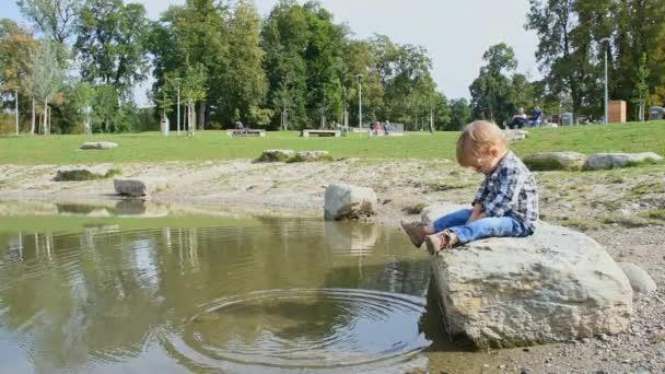 Netter kleiner Junge, der Spaß hat, Steine ins Wasser zu werfen. Freizeit- und lustige Outdoor-Aktivitäten für Kinder im Sommer