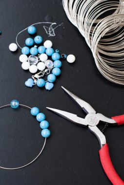 Turquoise and white beads, memory wire for bracelet, tools for creating fashion jewelry in the manufacturing process