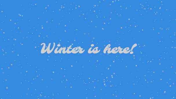 Zima je tady! Textový nápis na zasněženém pozadí. Sníh padající na modré pozadí.