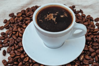 Cup of coffee and roasted beans on beige background