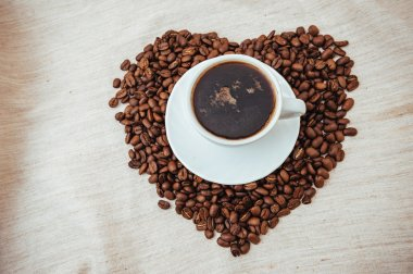 Cup of Coffee and roasted beans in heart shape isolated on white background.