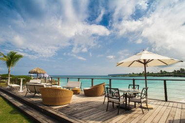Outdoor restaurant at the seashore. Table setting in tropical Summer Beach Cafe, ocean and sky. Dominican Republic, Seychelles, Caribbean, Bahamas. Relaxing on remote Paradise beach.
