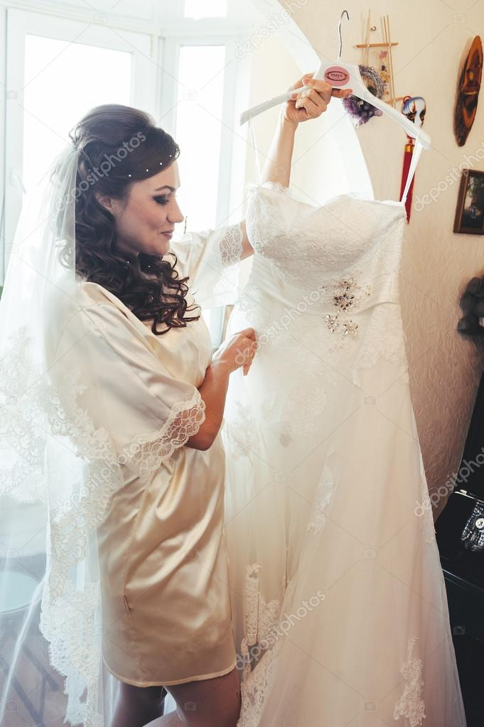 Happy beautiful bride tries on a wedding dress dressing gown. Girl ...