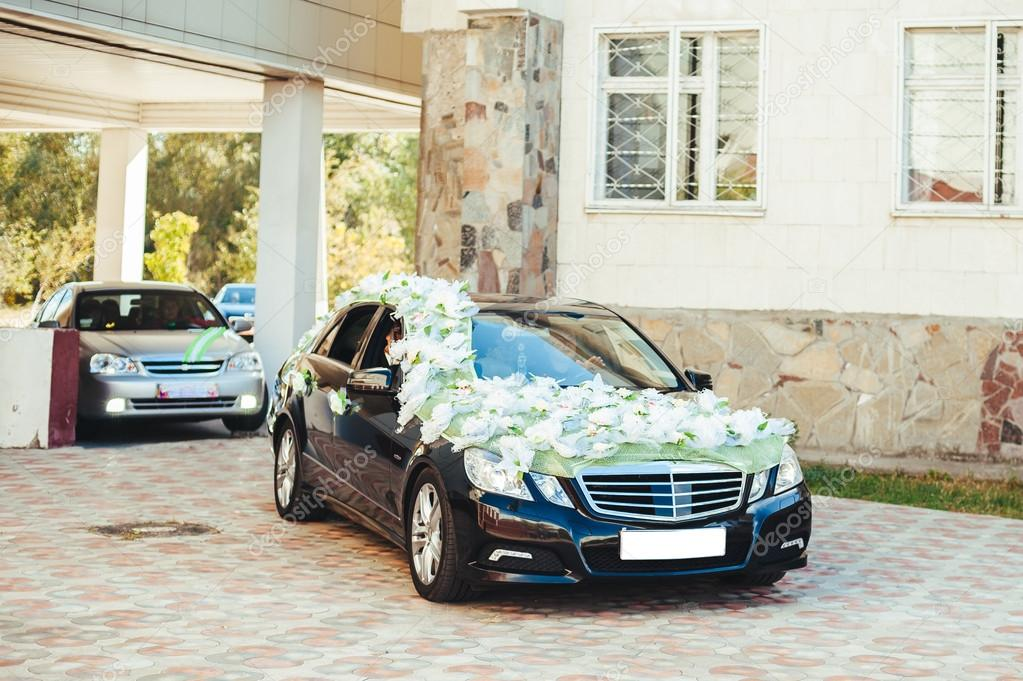 Black wedding car decorated with white roses