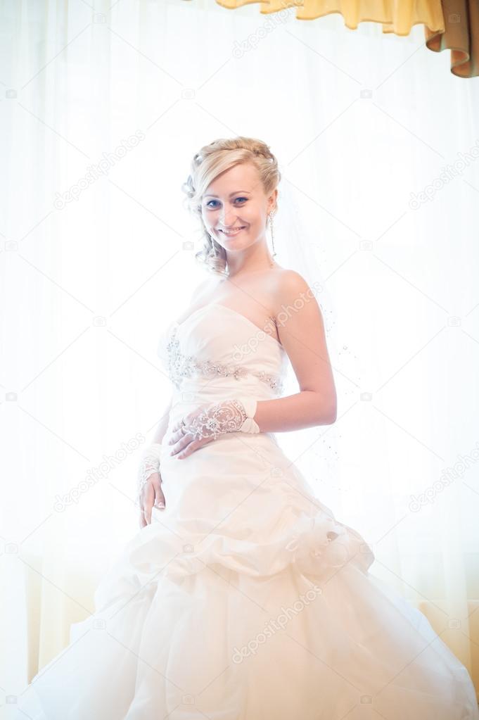 7868d870973cdb3 Невеста готовится. красивая невеста в белом свадебном платье с прической ...