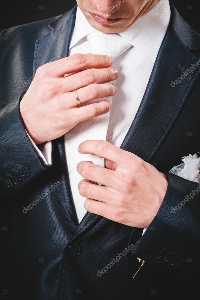 Manos del novio de la novia preparándose en traje. fondo negro ...