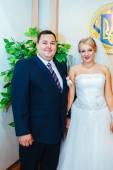 Svatební obřad. Matriční úřad. Novomanželé podepisuje dokument manželství. Mladý pár podpisu svatebních dokumentů