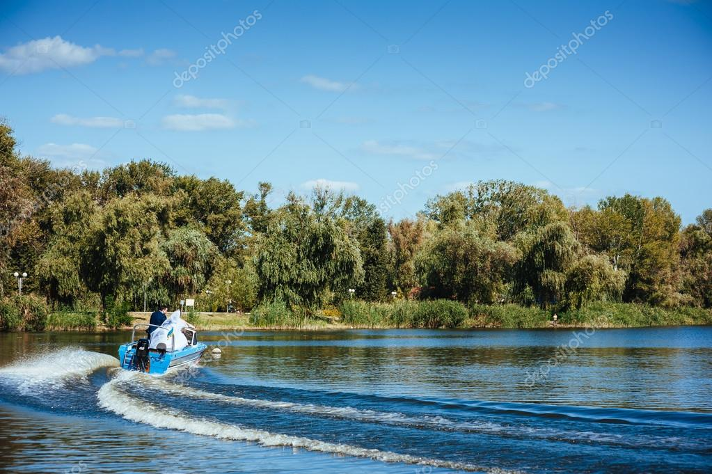 Фотообои Newly married couple riding in boat on river