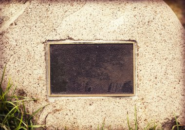 Weathered plaque in wall stone