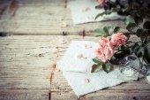 Růžové růže s brýlemi na dřevěný stůl