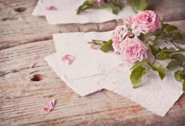 Pink roses with papers on wooden table