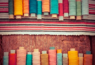 bobbins with threads and striped fabric