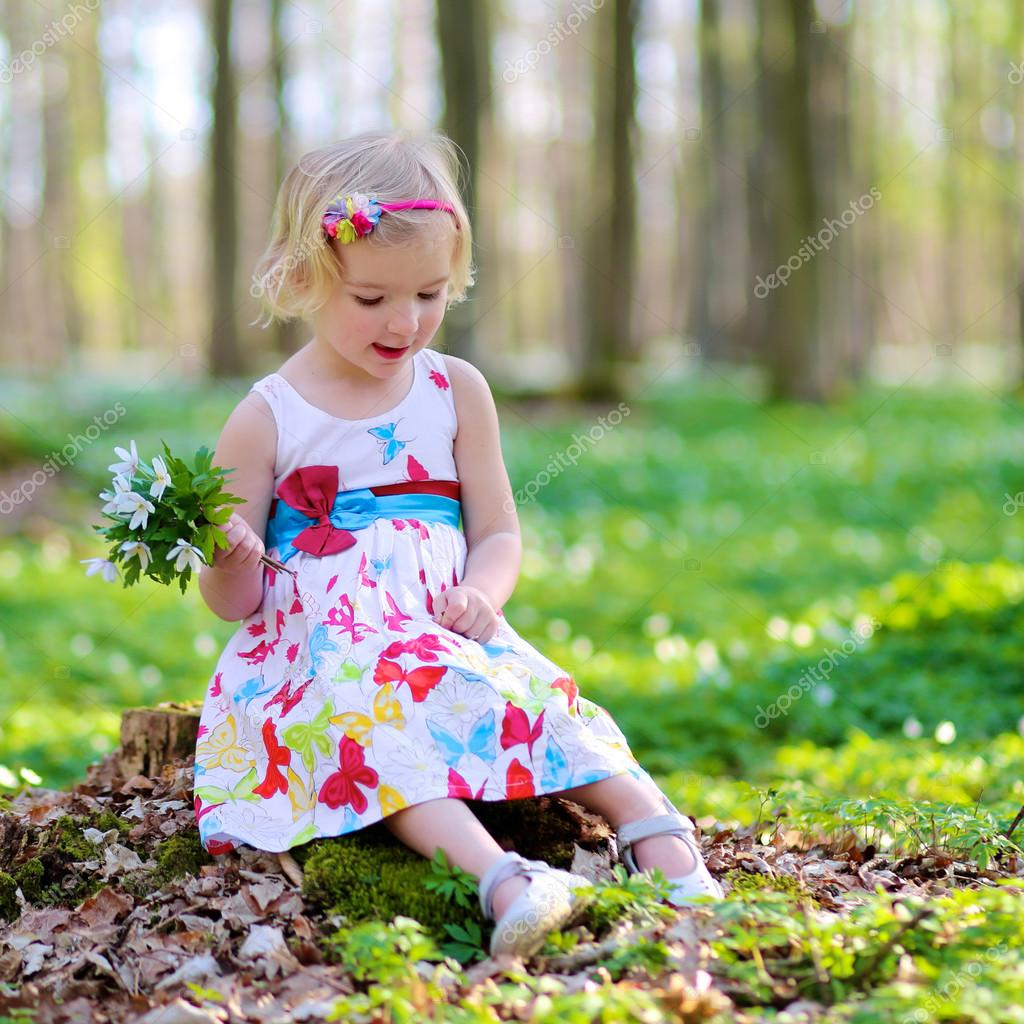 Little girl playing in beautiful forest